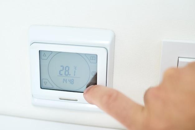 Męska ręka ustawia temperaturę na panelu sterowania ogrzewaniem podłogowym