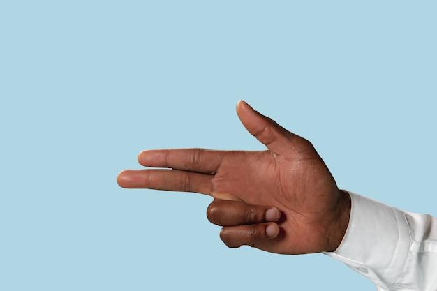 Męska ręka w białej koszuli demonstruje gest pistoletu, pistoletu lub pistoletu na białym tle na niebieskiej ścianie.