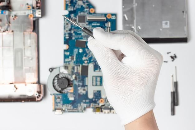 Męska ręka w białej rękawiczce trzyma w rękach śrubokręt na tle rozmontowanego laptopa.