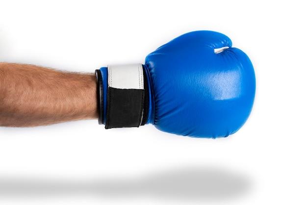 Męska ręka w błękitnej bokserskiej rękawiczce na bielu. kopnięcie boksu