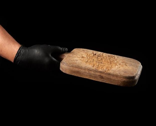 Męska ręka w czarnej rękawicy lateksowej trzymać pustą drewnianą deskę do krojenia vintage brązowy, czarne tło
