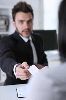 Męska ręka w kostiumu daje pustej karcie telefonicznej żeński gościa zbliżenie.