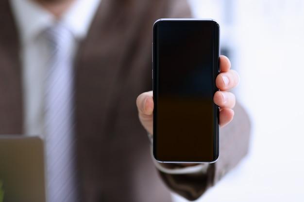 Męska ręka w kostiumu przedstawieniu w kamera telefonu pokazu ekranu zbliżeniu. czytaj wiadomości mania wyślij sms czat uzależniony używać elektronicznego banku nowoczesny styl życia plan pracy kolega dzielić blog tweet wyszukiwanie aplikacji internetowych