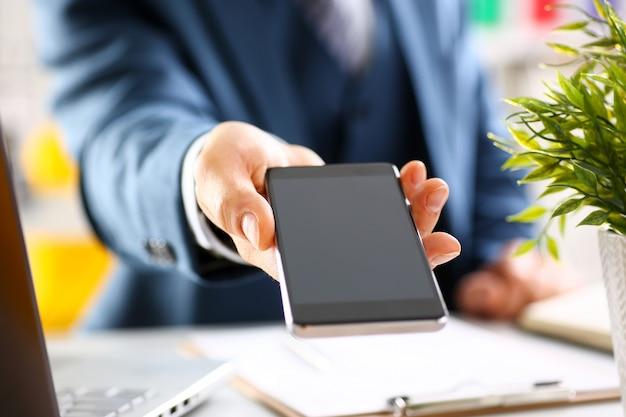 Męska ręka w kostiumu przedstawieniu w smartphone pokazu ekranu zbliżeniu