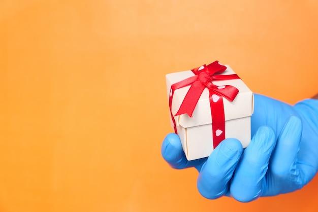 Męska ręka w niebieskiej rękawicy medycznej daje prezent.