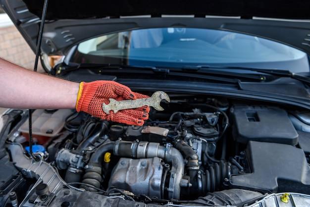 Męska ręka w rękawicy trzymająca klucze przeciwko silnikowi samochodowemu
