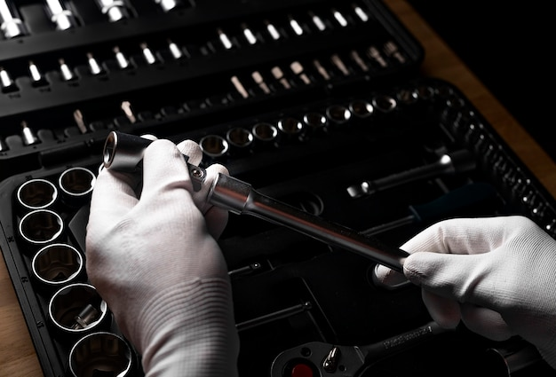 Męska ręka w rękawiczce trzymająca narzędzie do przedłużania metalowej rączki, zabierając ją ze skrzynki narzędziowej, walizki.