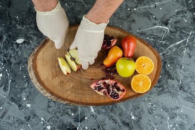 Męska ręka w rękawiczkach cięcia świeżego jabłka na marmurowym stole.