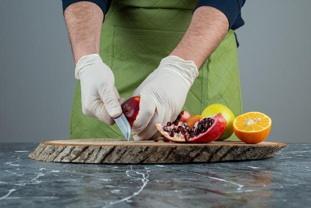 Męska ręka w rękawiczkach do cięcia czerwonego granatu na marmurowym stole.