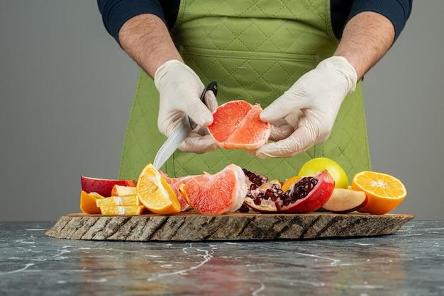 Męska ręka w rękawiczkach do cięcia soczystego grejpfruta na marmurowym stole.
