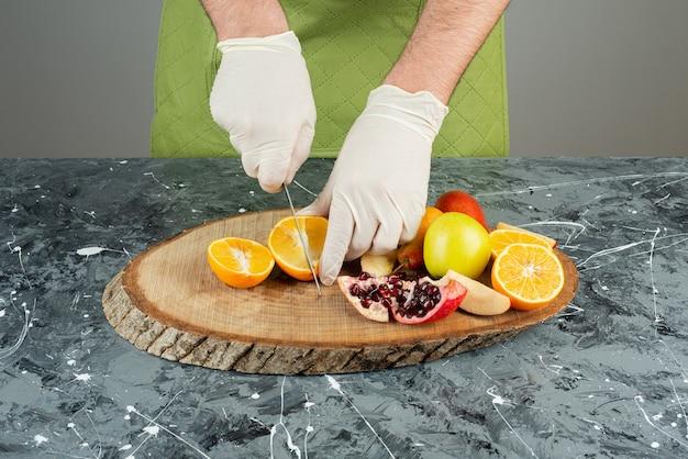 Męska ręka w rękawiczkach do cięcia soczystej pomarańczy na marmurowym stole.