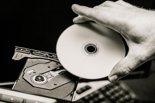Męska ręka wkłada dvd do napędu dyskowego. czarny i biały