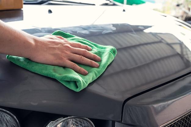 Męska ręka wycierająca plamę zieloną mikrofibrą na szarej masce samochodu