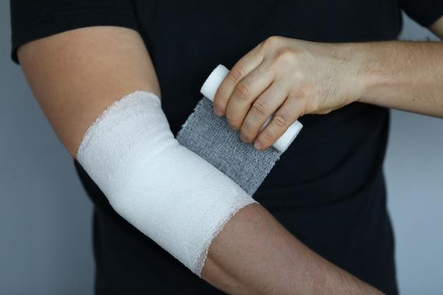 Męska ręka z ciasnym elastycznym bandażem na łokcia zbliżeniu