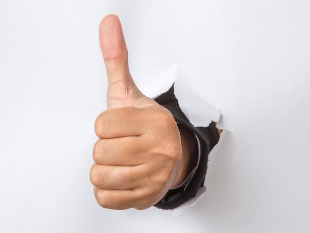Męska ręka z kciukiem w górę gestem uderza pięścią przez papieru