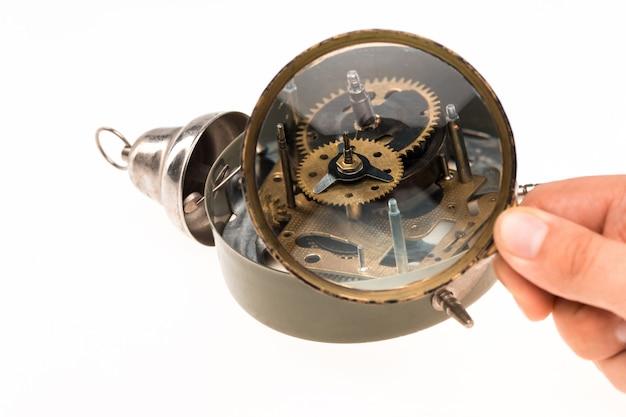 Męska ręka z lupą i mechanizmem zegarowym