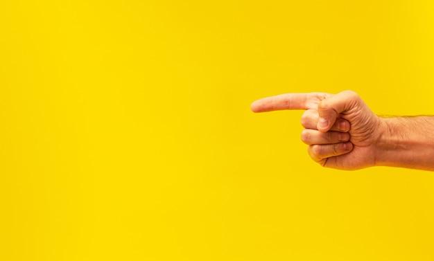 Męska ręka z palcem wskazującym na żółtym tle