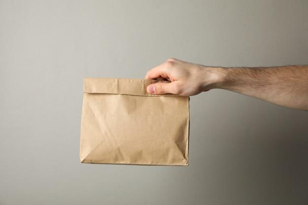 Męska ręka z papierowym pakunkiem przeciw szaremu tłu, przestrzeń dla teksta