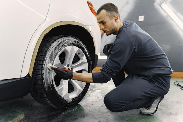 Męska ręka z piankową gąbką do mycia samochodu