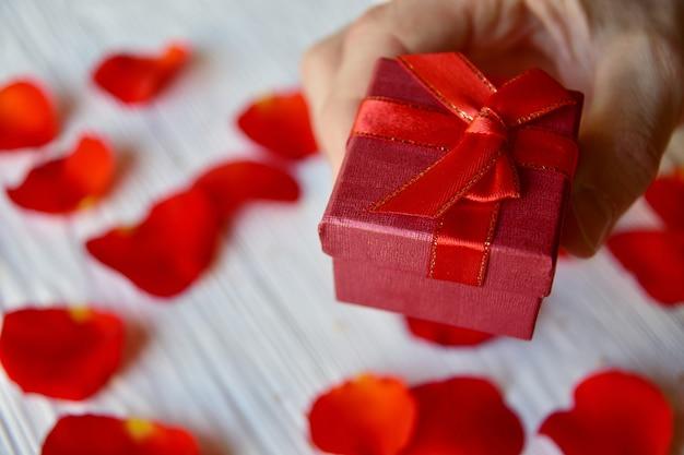 Męska ręka z pudełkiem prezentowym i czerwonymi płatkami róży. koncepcja walentynki