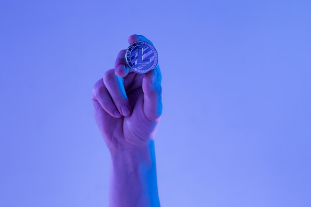 Męska ręka z złotym litecoin na błękitnym tle