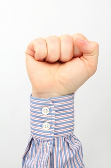 Męska ręka zaciśnięta w pięść na biało
