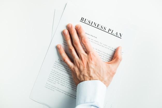 Męska ręka zakrywa dokument na stole. ostateczna decyzja. przyjęcie.