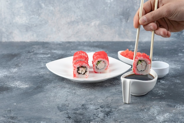 Męska ręka zbiera rolkę sushi pałeczkami na marmurowym tle