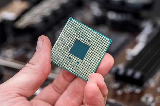Męska ręka zdejmująca układ procesora z płyty głównej