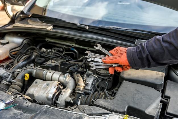 Męska ręka ze stalowymi kluczami na silniku samochodowym