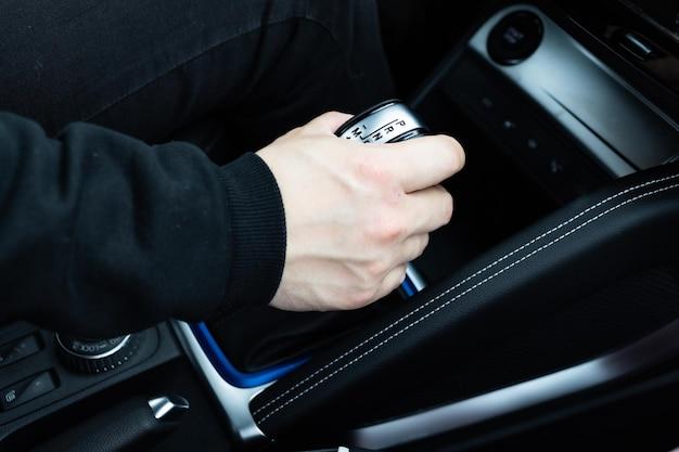 Męska ręka zmienia biegi na dźwigni automatycznej skrzyni biegów