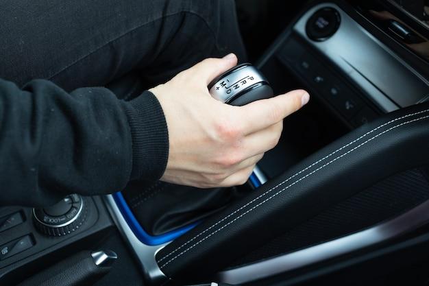 Męska ręka zmienia biegi w widoku kąta dźwigni automatycznej skrzyni biegów