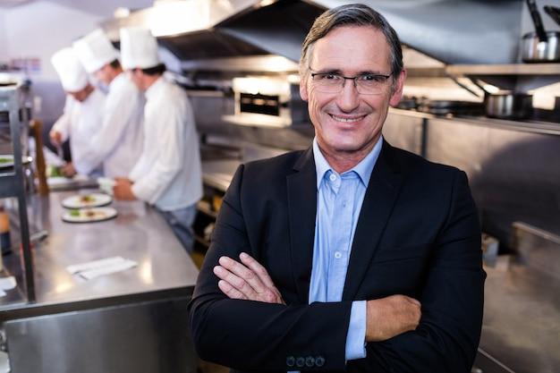 Męska restauracyjna kierownik pozycja z rękami krzyżować