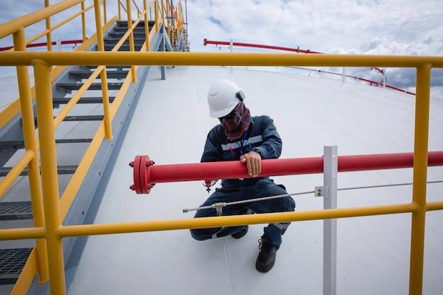 Męska rura inspekcyjna pracownika rozpyla zbiorniki przeciwpożarowe gaz propanowy dachowy zbiornik z gaśnicą i układem chłodzenia.