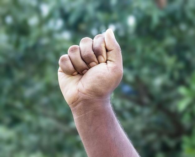 Męska silna ręka pięści rozciągająca się na miękkim zielonym tle bokeh
