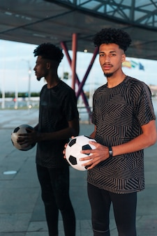 Męska sportowiec pozycja z futbolem na odzwierciedlającym tle