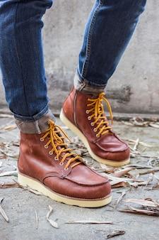 Męska stopa z brązowymi skórzanymi butami i dżinsami