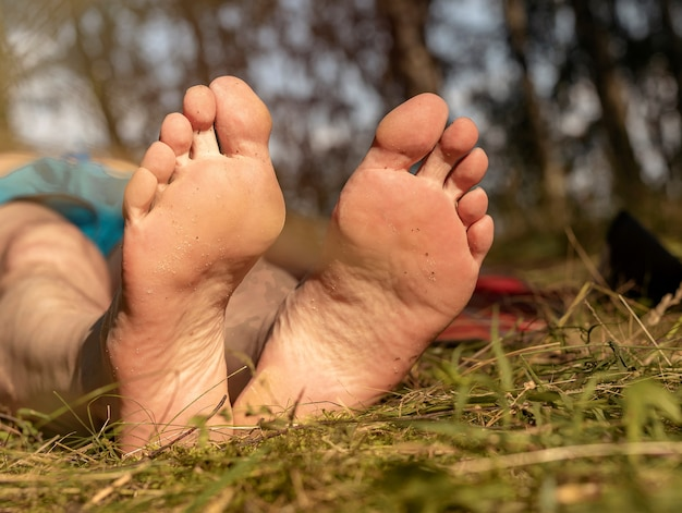 Męska stopa z obcasami na trawie w słoneczne lato na zbliżenie dobrej pogody