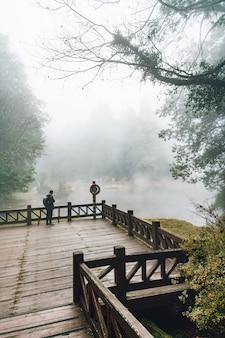 Męska turystyczna pozycja na drewnianej platformie z cedrowymi drzewami i mgłą w lesie w alishan.