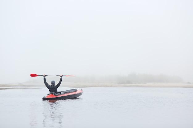 Męska wyściółka w rzece, siedząc w kajaku z podniesionym wiosłem, ciesząc się sportami wodnymi i piękną przyrodą, ubrany w czarną kurtkę i szarą czapkę