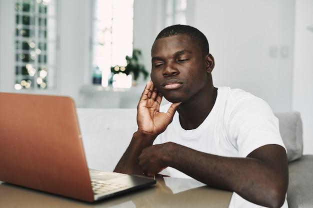 Męski amerykanina afrykańskiego pochodzenia freelancer z laptopem w domu