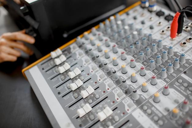Męski aranżer muzyczny współpracuje ze wzmacniaczem dźwięku, komponuje utwory na pianinie midi i sprzęcie audio w cyfrowym studiu nagrań