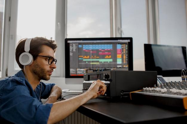 Męski aranżer muzyki współpracuje ze wzmacniaczem dźwięku