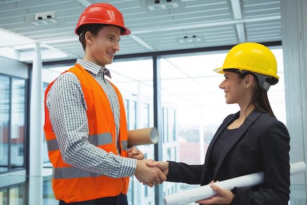 Męski architekt, ściskając ręce z bizneswoman