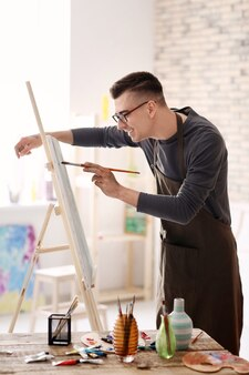 Męski artysta malujący na płótnie w warsztacie