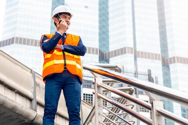 Męski azjatycki kierownik budowy z używać walkie-talkie przy budową.