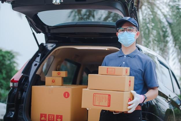 Męski azjatycki personel dostawczy trzymał kartonowe pudełko klienta. pracownicy dostawy noszą maski ochronne i rękawice ochronne.
