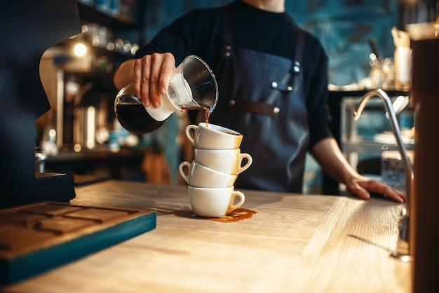 Męski barista nalewa czarną kawę na stos filiżanek