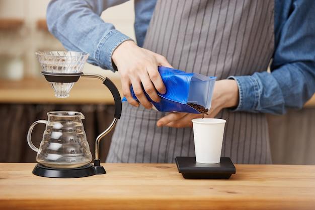 Męski barista parzący kawę pouron, skalujący kawę ze skalą cyfrową.