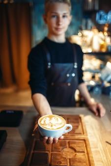 Męski barista pokazuje filiżankę kawy z rysunkiem pianki